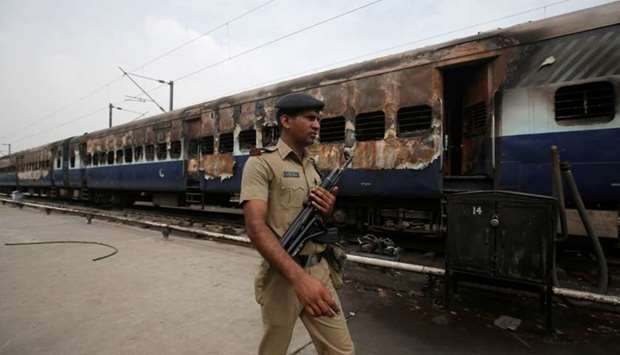 A security personnel member walks past a burnt carriage of a train near a railway station in New Del