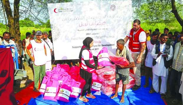 One of the victims receive a relief kit from Qatar Red Crescent staff