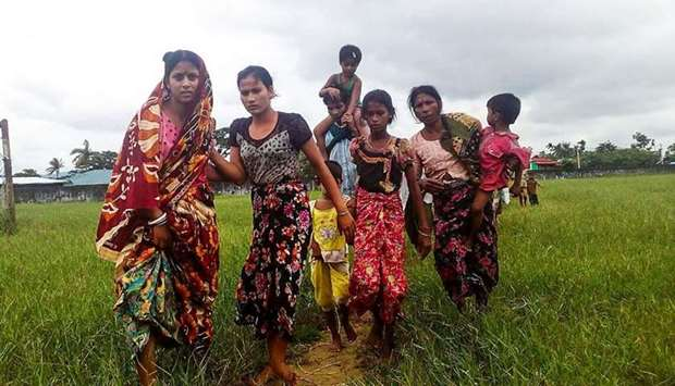 Women and children fleeing violence in their villages arrive at the Yathae Taung township in Rakhine