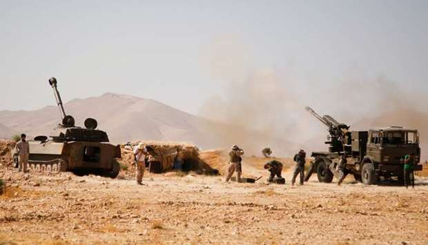 Hezbollah fighters stand near military tanks in Western Qalamoun, Syria on August 23, 2017.