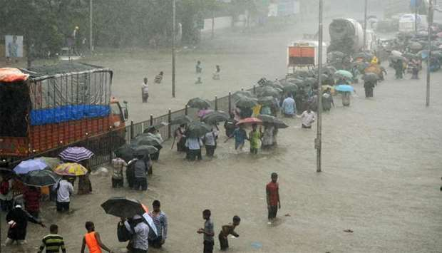 Indians wade through a flooded street during heavy rain showers in Mumbai