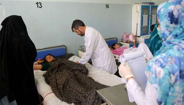 An injured Afghan woman receives treatment at a hospital following an airstrike in Herat