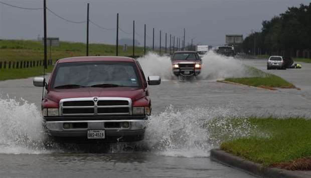 Vehicles drive along a flooded road in Houston