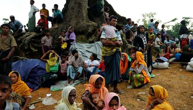 New Rohingya refugees sit near the Kutupalang makeshift refugee camp, in Cox's Bazar