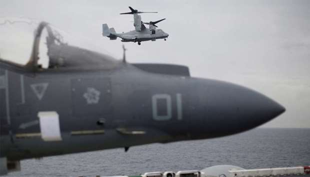 US Marines MV-22 Osprey Aircraft flies over a jet before landing on the deck