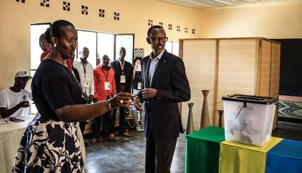 Incumbent Rwandan President Paul Kagame and his wife Jeannette arrive to cast their vote at a pollin