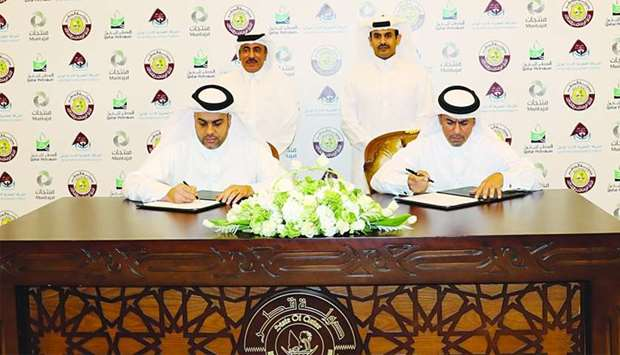 Al-Khanji and al-Abdulla sign the MoU between Mwani Qatar and Muntajat in the presence of HE al-Sula