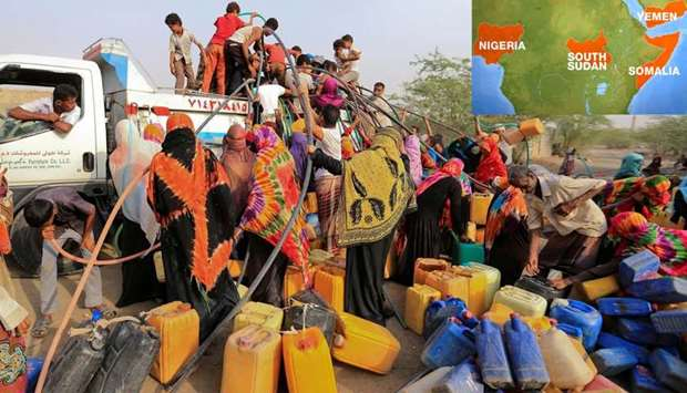 People gather around a charity tanker truck to fill up their jerrycans with drinking water in Yemen