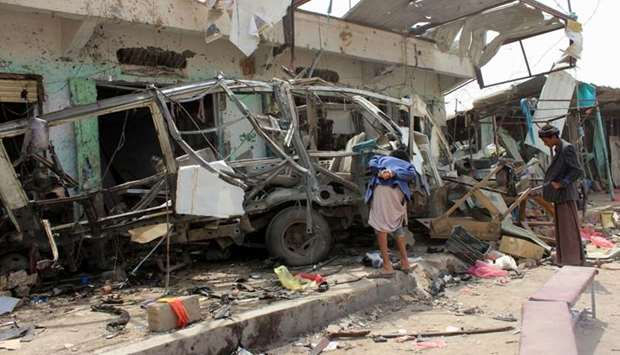 Yemenis gather next to the destroyed bus at the site of a Saudi-led coalition air strike, that targe