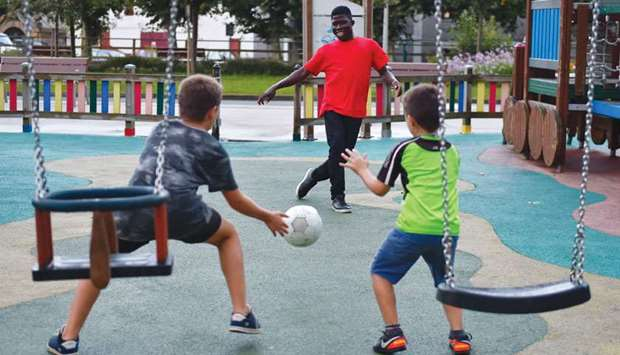 A migrant plays football with local children outside a migrants reception centre in Irun.