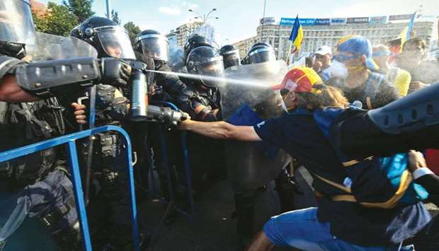 Police scuffle with protesters using teargas during an anti-government protest in front of the Roman