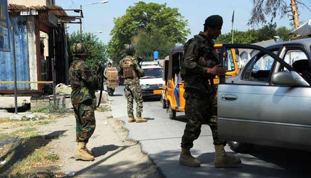 Afghan National Army (ANA) soldiers search vehicles at a checkpoint in the city of Jalalabad.