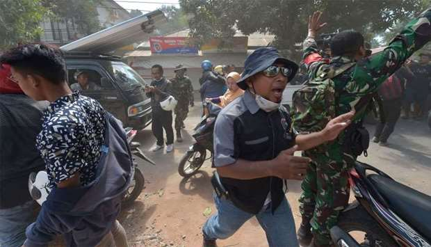 An Indonesian soldier (R) and an official (C) try to calm people shortly after an aftershock hits th