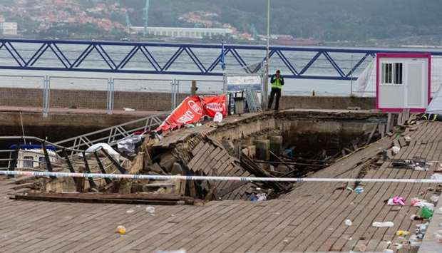 A police investigator inspects the seafront platform in Vigo after a section of a wooden promenade s