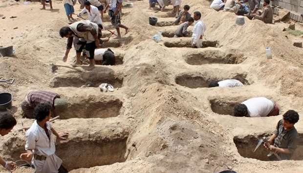 Yemenis dig graves for children, who where killed when their bus was hit during a Saudi-led coalitio