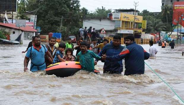 Indian volunteers and rescue personal evacuate local residents in a boat in a residential area at Al