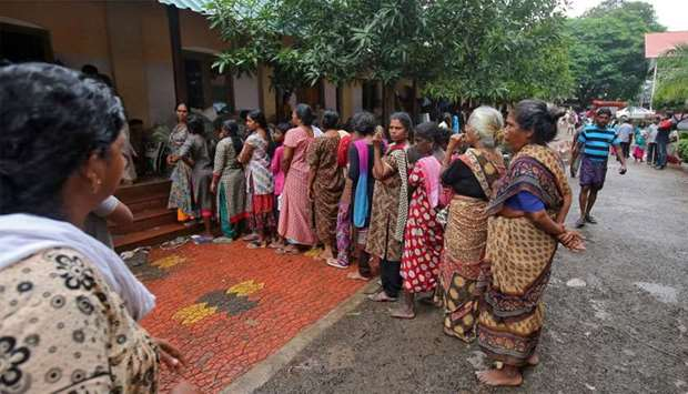Flood-affected women wait in a queue to receive relief material at a camp in Chengannur