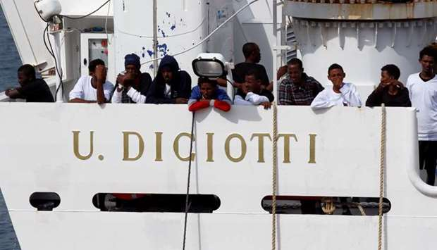 """Migrants waits to disembark from Italian coast guard vessel """"Diciotti"""" as they arrive at the port of"""