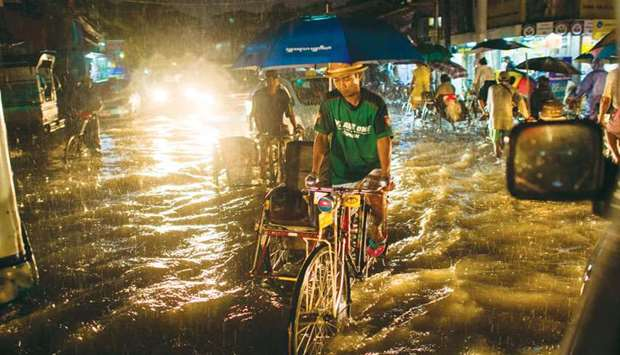 A man rides a tri-shaw along a flooded road in Yangon yesterday.