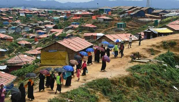 Rohingya refugee volunteers walk along Balukhali refugee camp in Ukhia district near Cox's Bazar.