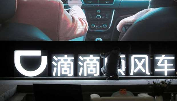 A man is seen in front of a Didi sign before a promotional event of its Hitch service