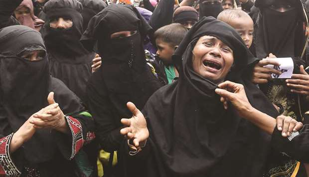 Rohingya refugees burst into tears during a protest march after attending a ceremony to remember the