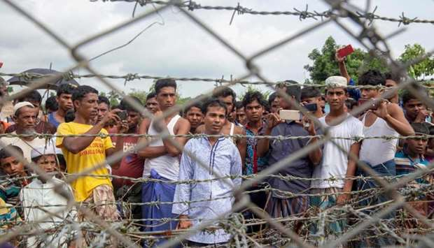 "Rohingya refugees gather near the fence in the ""no man's land"" zone between Myanmar and Bangladesh b"