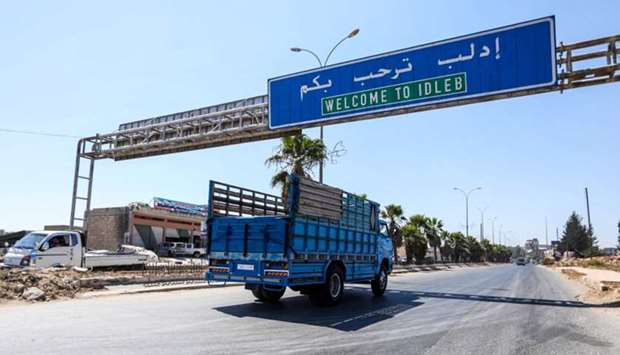 A truck drives past underneath a sign along the highway leading to the rebel-held northern Syrian ci