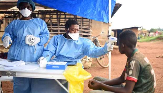 Congolese health workers take the temperature of a civilian before administering the Ebola vaccinati