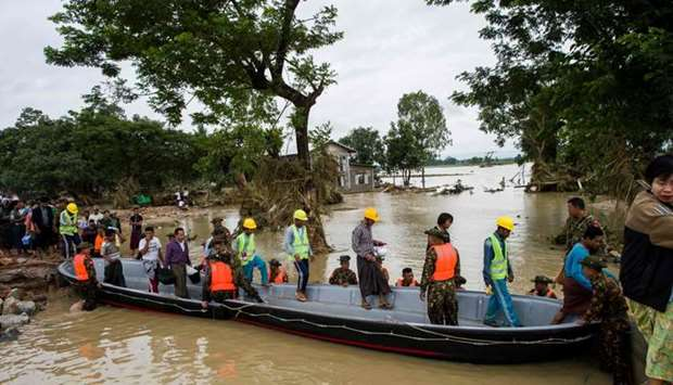 Myanmar soldiers use a boat to help residents cross a flooded area in Swar town of Bago region