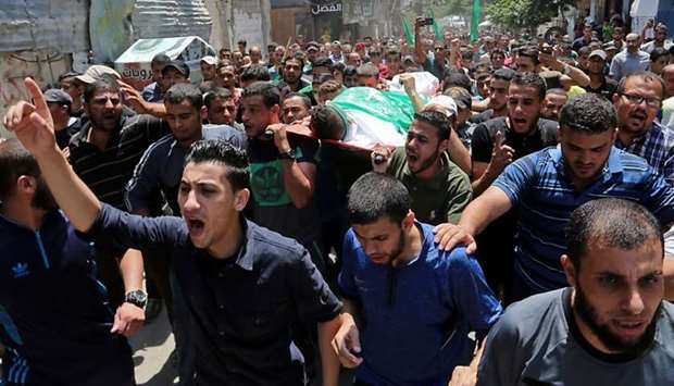 Palestinian mourners carry the body of Muadh al-Suri