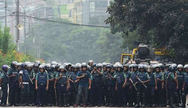 Bangladeshi police stand guard during a student protest in Dhaka