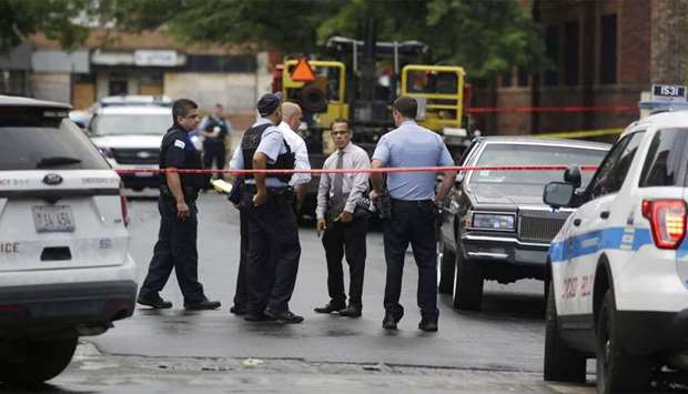 Chicago Police officers and detectives investigate a shooting where multiple people were shot in Chi