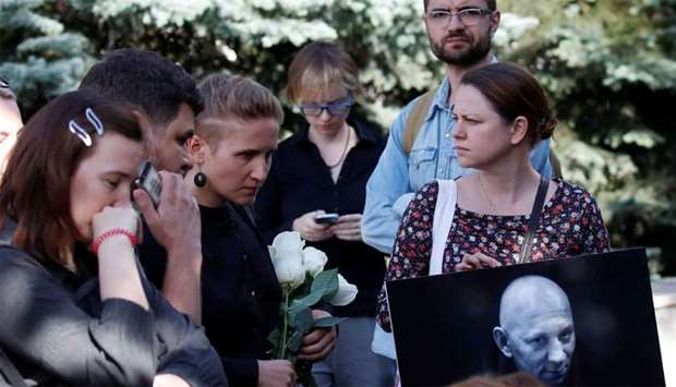 People mourn during a funeral ceremony for Rastorguyev, one of three Russian TV journalists killed i