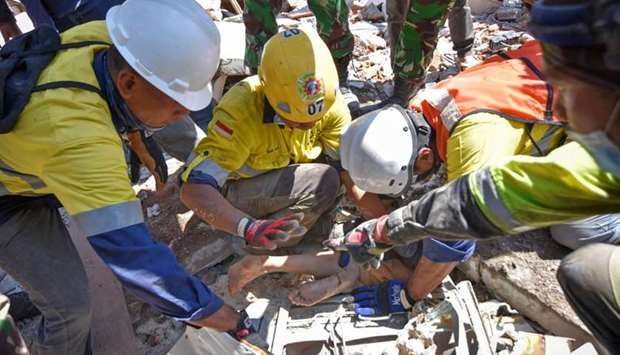 Rescue workers extract a woman, who survived after being trapped in rubble since Sunday's earthquake
