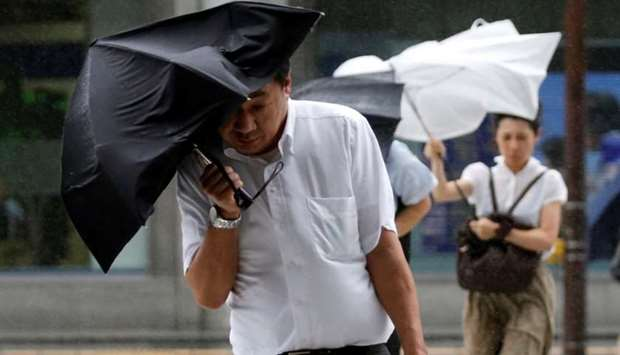 Passersby using an umbrella struggle against a heavy rain and wind as Typhoon Shanshan approaches Ja