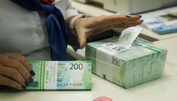 A cashier holds new 200 rouble banknotes in a bank in Moscow