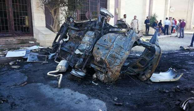 People gather at the site where a car bomb exploded in Benghazi, Libya
