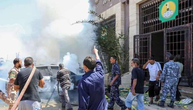 Libyan firefighters extinguish a fire at the site of car bomb attack in Libya's eastern city of Beng
