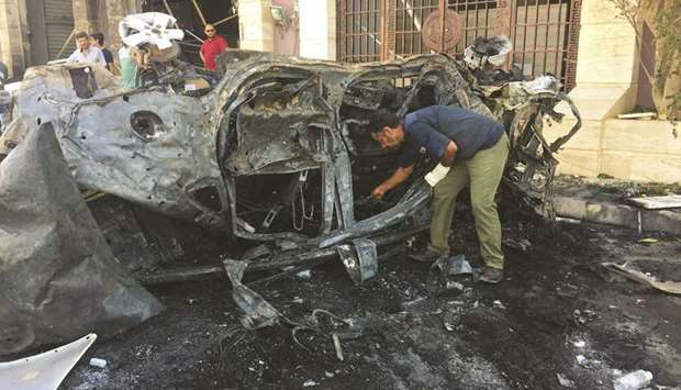 A security official inspects the site where a car bomb exploded in Benghazi yesterday.