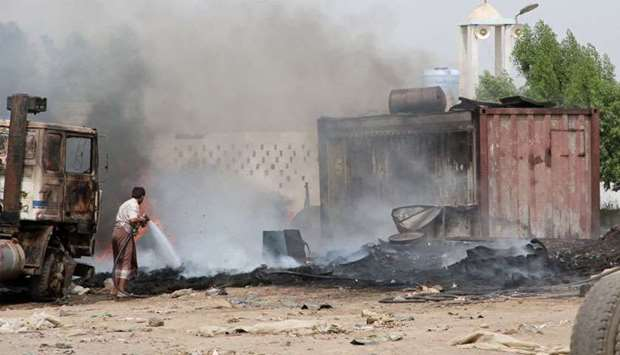 Man extinguishes fire at a car service shop during clashes in Aden