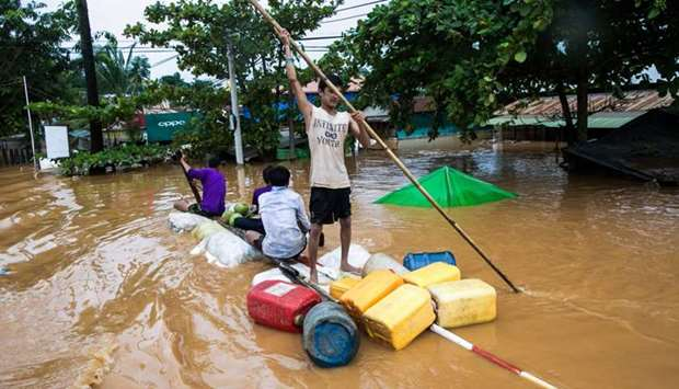 Residents use an improvised raft as floodwaters submerged areas of Ye township in Mon State