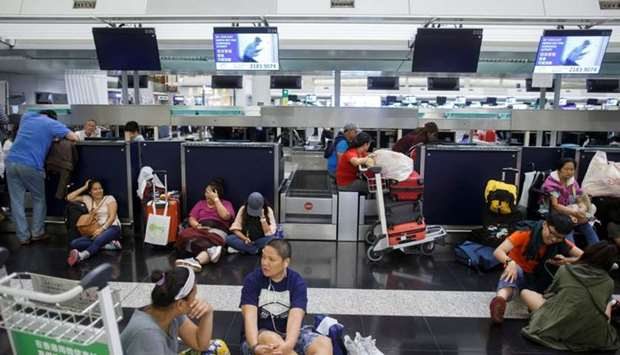 Passengers rest at the check-in counters after all flights were cancelled due to a protest inside th