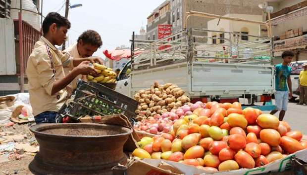 A fruit peddlar sells produce from a cart along a market street in the Crater district in the centre