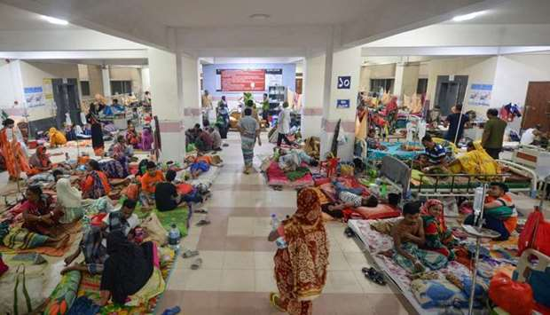 Bangladeshi patients suffering from dengue fever rest on the floor of a ward at the Mugda Medical Co