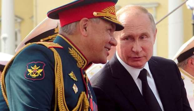 Russian President Vladimir Putin speaks to Defence Minister Sergei Shoigu as they watch the military