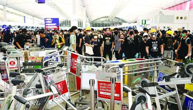 Pro-democracy protestors block the entrance to the airport terminals after a scuffle with police at