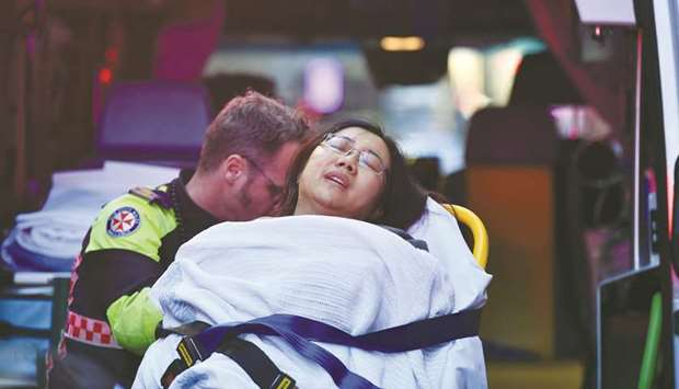 A woman is taken by ambulance after a man stabbed a woman and attempted to stab others in central Sy