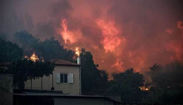 Flames rise next to a house as a wildfire burns at the village of Kontodespoti, on the island of Evi