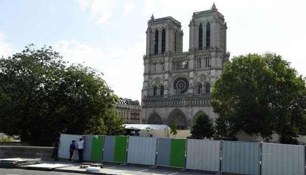 Workers install pallissades in front Notre-Dame cathedral in Paris before a decontamination work